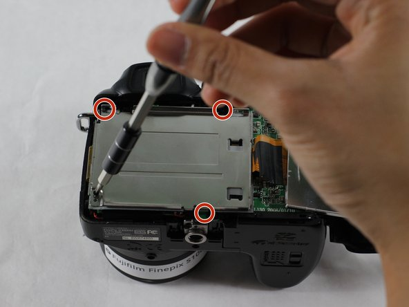 Use the PH00 screwdriver to unscrew the 0.5mm screws located near the top left corner, top right corner, and bottom right corner.
