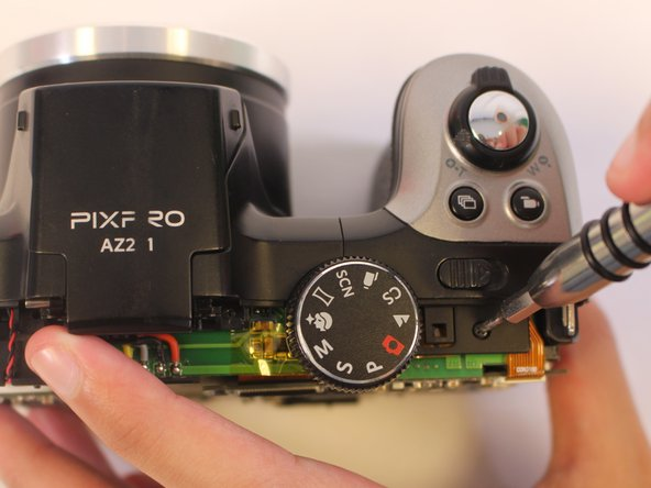 Remove one 4mm JIS #000 screw from the top of the camera.