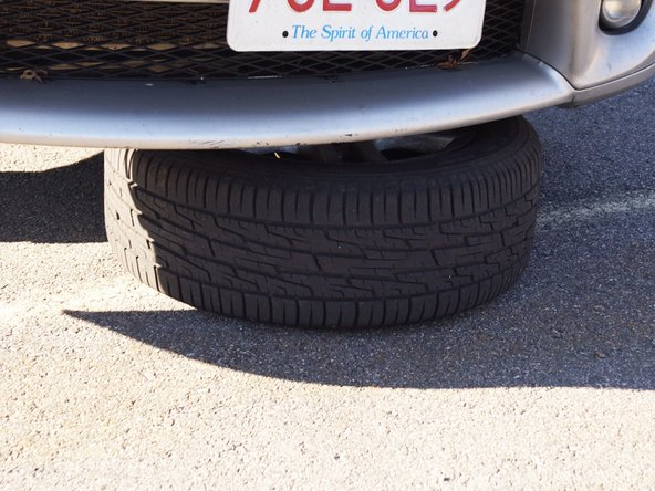 Image 1/1: For safety, place the tire under the vehicle in case the jack fails. ''You may also use a jack stand instead of the tire,if you have one.''