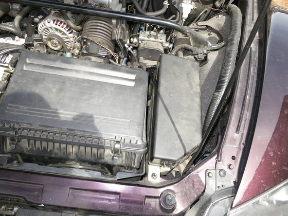 Put the fuse box cover back on and secure the tabs on the side.