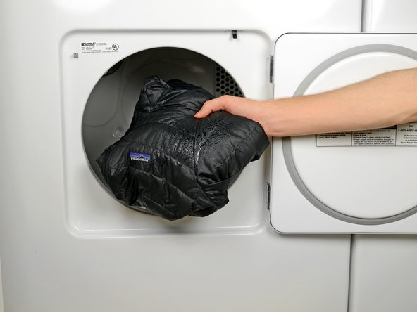 Remove the jacket from the washing machine and place it in the dryer.