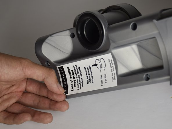 Peel the sticker away with your hands until the hidden screw hole is fully exposed.