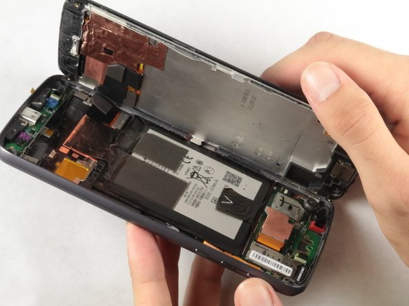 Use a metal spudger to remove the connector located above the battery on the rear case.