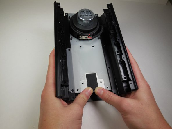 Image 2/2: Slide the tray containing the subwoofer out of the housing.