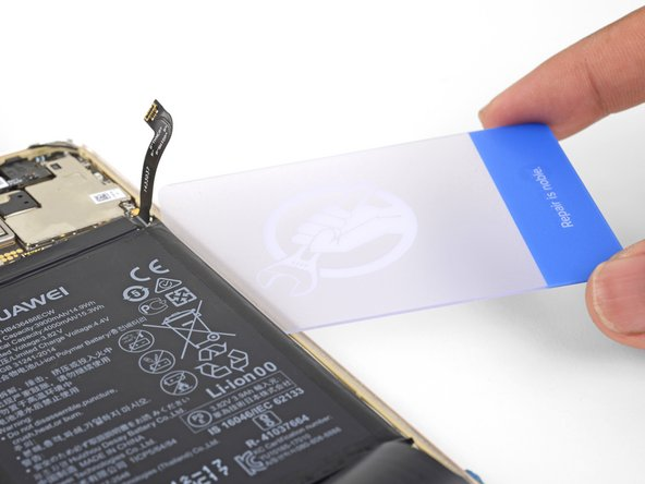 Insert a plastic card under the battery's right edge.