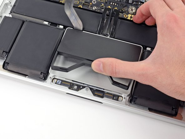 While holding the spring bar depressed, tilt the SSD assembly up out of its cavity.