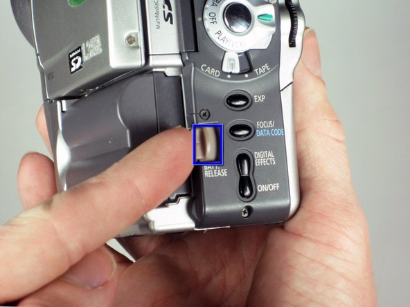 Orient the camera so that the back button panel and viewfinder are facing you.