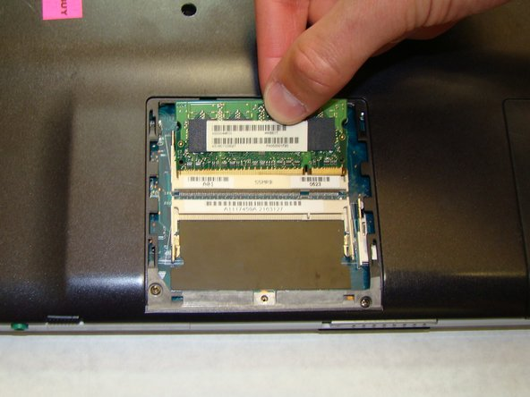 Image 2/3: Use your fingers to grab the raised edge of the RAM and pull the chip away from its connection to the laptop.