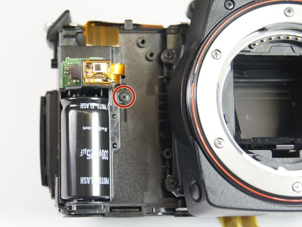 Remove the 5.0 mm Phillips #00 screw on the right side of the flash capacitor.