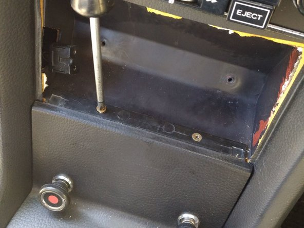 Now you can remove those two counter-sunk screws holding in the front of the shifter/center console panel.