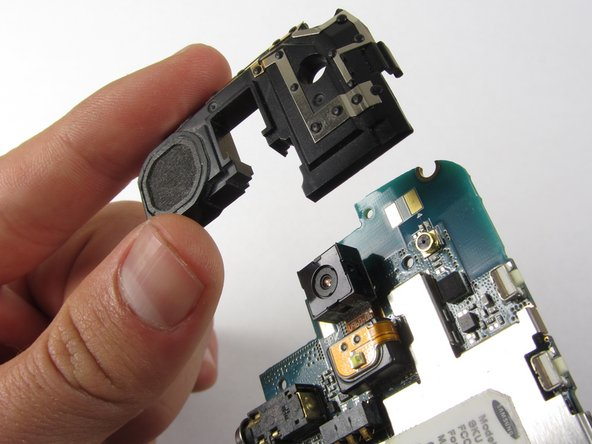 Use a plastic opening tool to pop off the edges of the speaker/antenna piece from the motherboard.