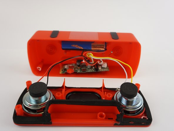 Gently pull apart the speaker to separate the speakers from the battery and motherboard. Then pull out the motherboard with your fingers by grabbing the edges and pulling upwards.