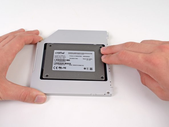 Image 3/3: While firmly holding the enclosure in place with one hand, use your other hand to press the hard drive into the enclosure connectors.