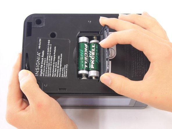 Image 3/3: Lift the battery cover up and to the right to reveal the batteries.
