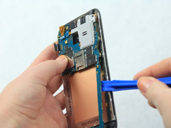 Lift the motherboard from the phone with an iFixit Opening Tool.