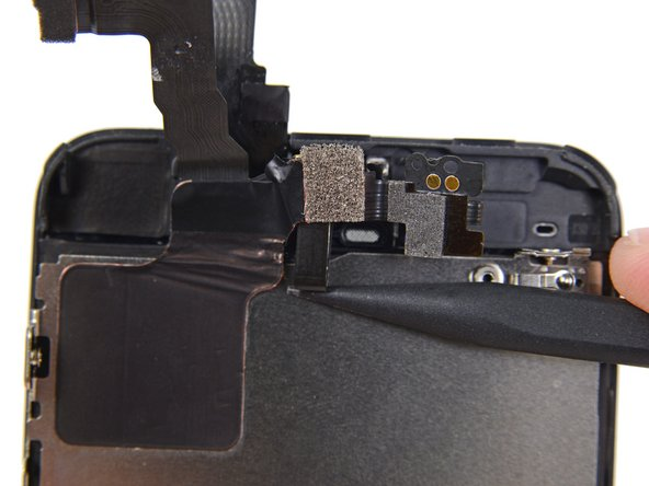 Gehe mit der Spitze eines Spudgers unter das Mikrofon, um es aus seiner Vertiefung im Display zu hebeln.