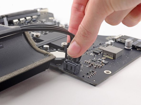 Image 3/3: While pressing on the clip with your thumb, lift and disconnect the SATA data connector from its socket on the logic board.