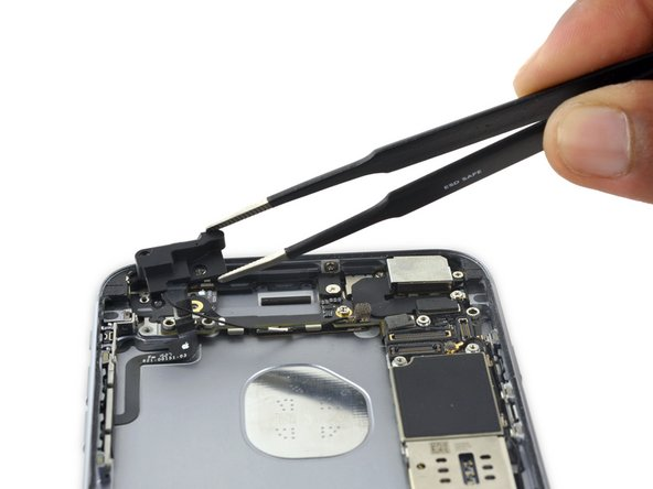 Lift, but do not remove, the cellular antenna to reveal the third screw securing the audio control cable to the rear case.