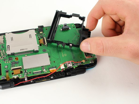 Remove the battery housing by lifting it away from the charging port.