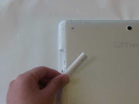 With the device face down, slide the charging port cover off on the left side of device.