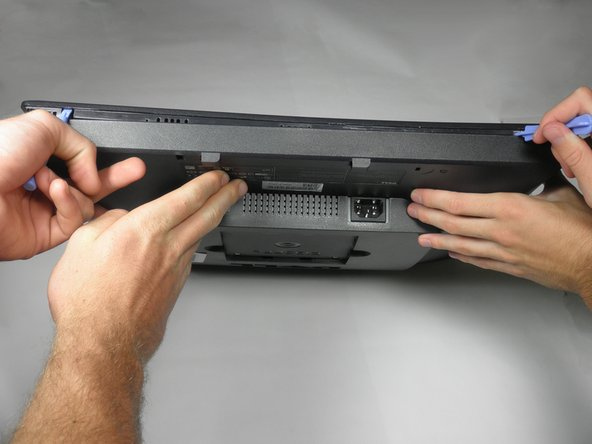 Insert a plastic opening tool or spudger into the holes and gently pry the plastic apart along the groove.