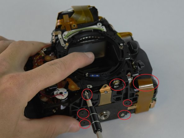 Several screw and ribbon cables and the bottom portion of the camera need to be removed as shown in the picture