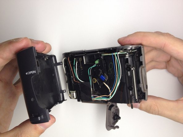 Image 2/3: Gently remove the back of the camera case with a slight twisting motion.