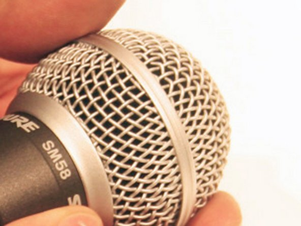 Hold the body of the microphone, right below the grille, in one hand. Using your other hand, rotate the grille clockwise.