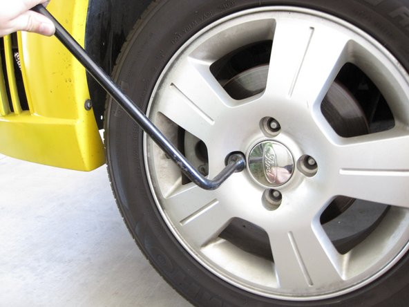 Use a lug wrench to completely remove the four lug nuts.
