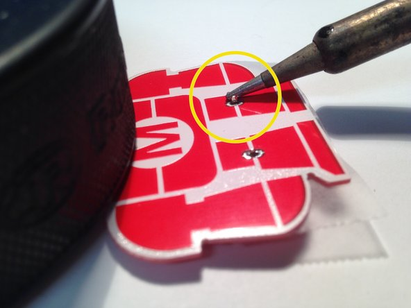Rest the iron between the extruding battery holder tab and the corresponding solder pad to begin heating them up.