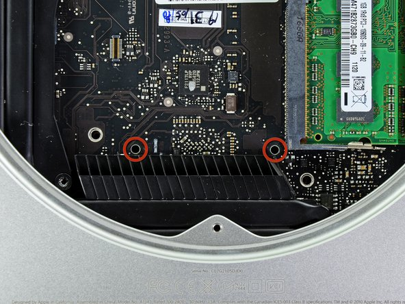 To remove the logic board, the two cylindrical rods of the Mac Mini Logic Board Removal Tool must be inserted into the holes highlighted in red. Inserting instruments into any logic board holes other than the ones highlighted in red may destroy the logic board.