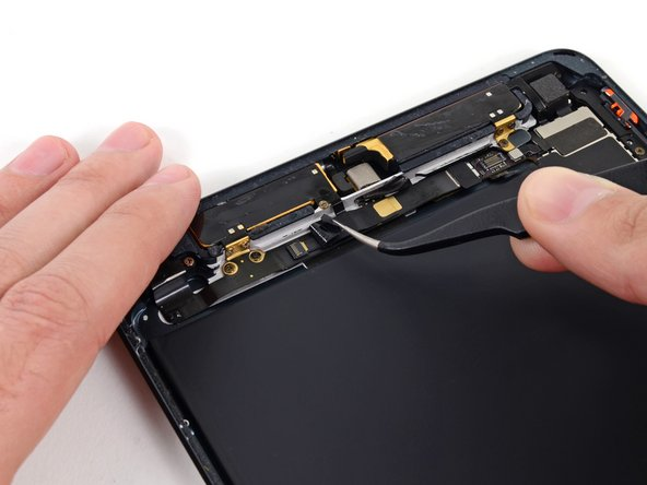 Use tweezers to peel and remove the long thin black tape covering the top of the headphone jack cable.