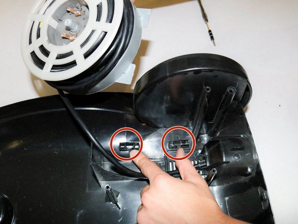 Pull on cord reel to remove it. You should hear a click indicating it has detached from the area indicated in the picture.