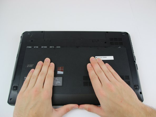 Using both hands, slide the plate off of the back of the laptop.