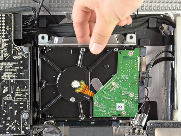 Image 2/2: Slightly rotate the top edge of the hard drive away from the outer case.