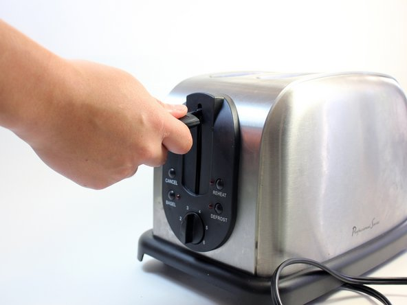 Grip the black plastic lever nub firmly and carefully remove it from the metal lever. Use one hand to hold the toaster in place while you pull the lever nub with the other.