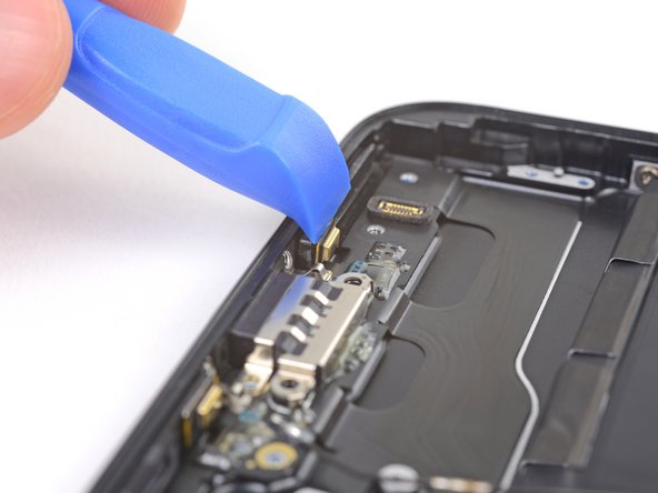 Use the sharp edge of an iFixit Opening Tool to pry the two microphones free from the adhesive securing them in place.