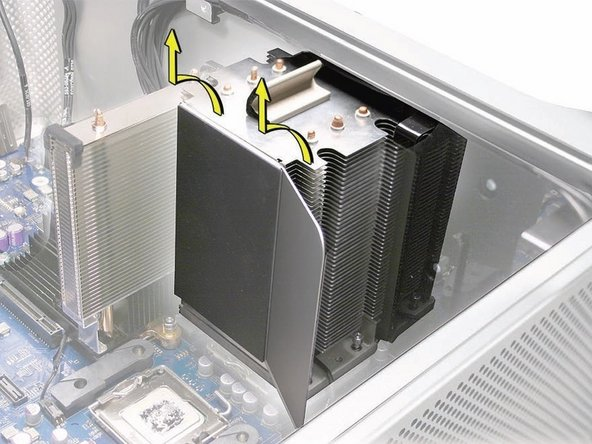 Image 2/2: Carefully tilt the heatsink so that it clears the bottom lip of the enclosure and then lift the heatsink out of the computer.