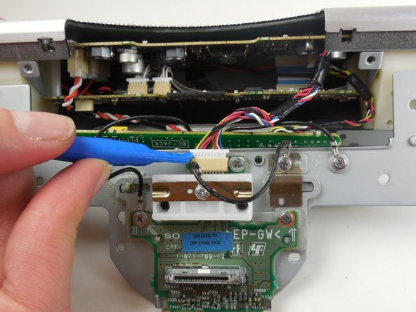 Using the plastic opening tool, detach the wires connected to the metal plate