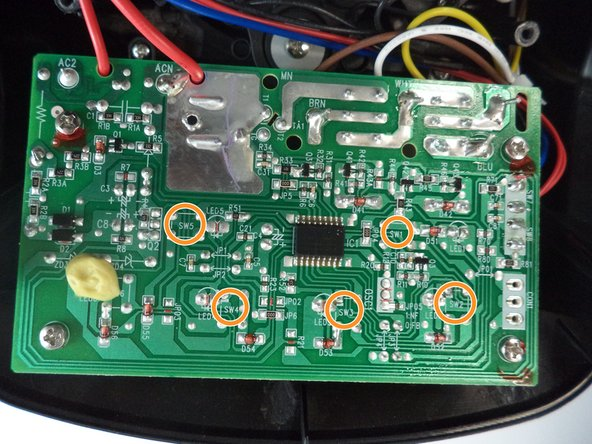 """On the back of the circuit board from the button, there are four solder pads with the designation """"SW"""" followed by a number."""