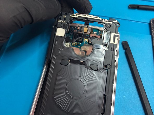 Use a spudger to remove the charging coil from the top left corner,