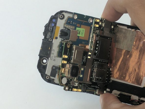 Image 2/3: Now gently pull the motherboard away from its housing. You'll now want to have access to its bottom side.