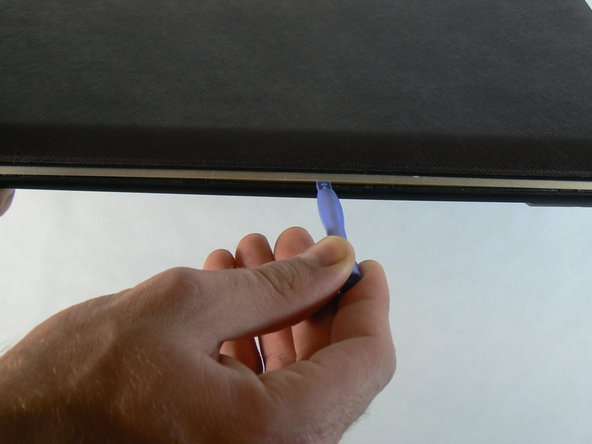 Use the blue plastic opening tool to pry the silver plastic keyboard surround out from the black plastic bottom. You will need to do this around the entire perimeter of the laptop and will hear a pop every time one of the retention clips is unlatched.
