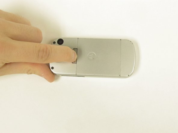 Pinch the latch upwards towards the top of the phone.