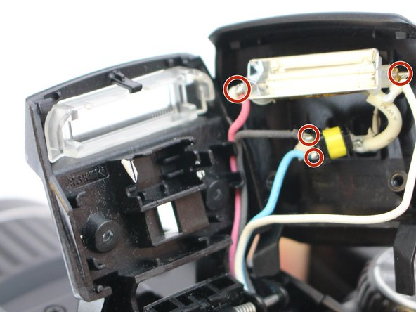 Unsolder the connections shown in the image that connect the black, pink, white and blue wires to the bulb.