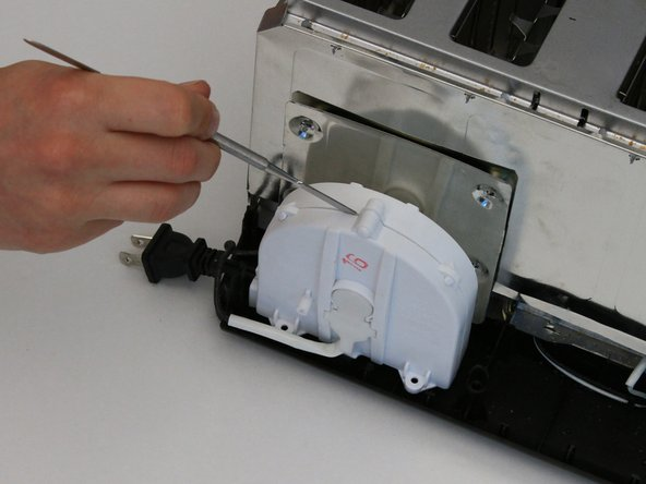 Image 1/2: Use the metal spudger to pry open the two halves of the casing.