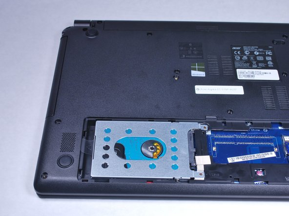 Grab hold of the plastic tab and pull the hard drive away from the connectors. This will release the hard drive.