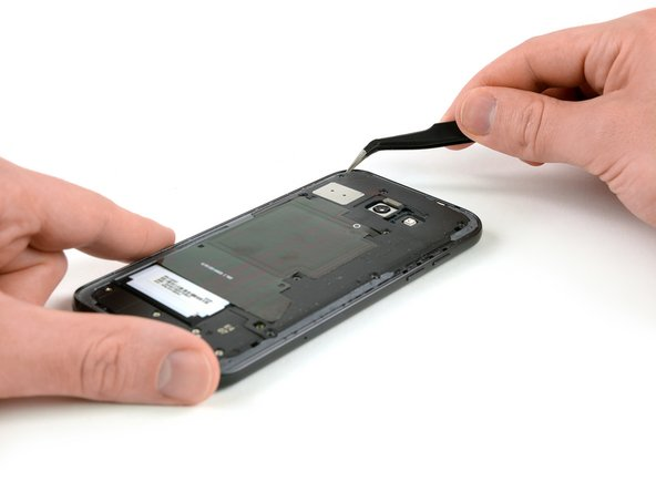 Use a pair of tweezers to lift the mother board cover on both upper corners of the phone  out of its clamps.