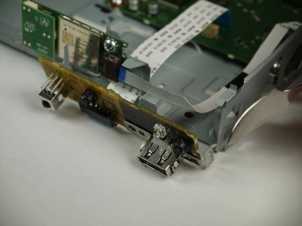 Using the nylon or metal spudger, carefully unclip the port board from the side of the player.
