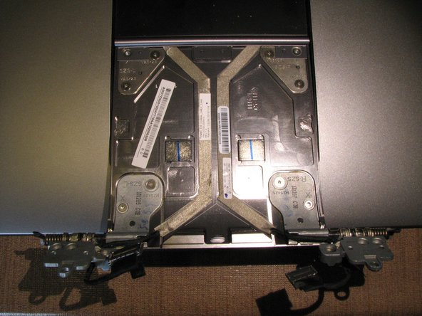 Image 3/3: Remove the 4 T9 torx screws from the display assembly where the model number and serial numbers stickers are located and swap that panel to the replacement display assembly.  Completing this step allows for your computer to retain its original identification information.